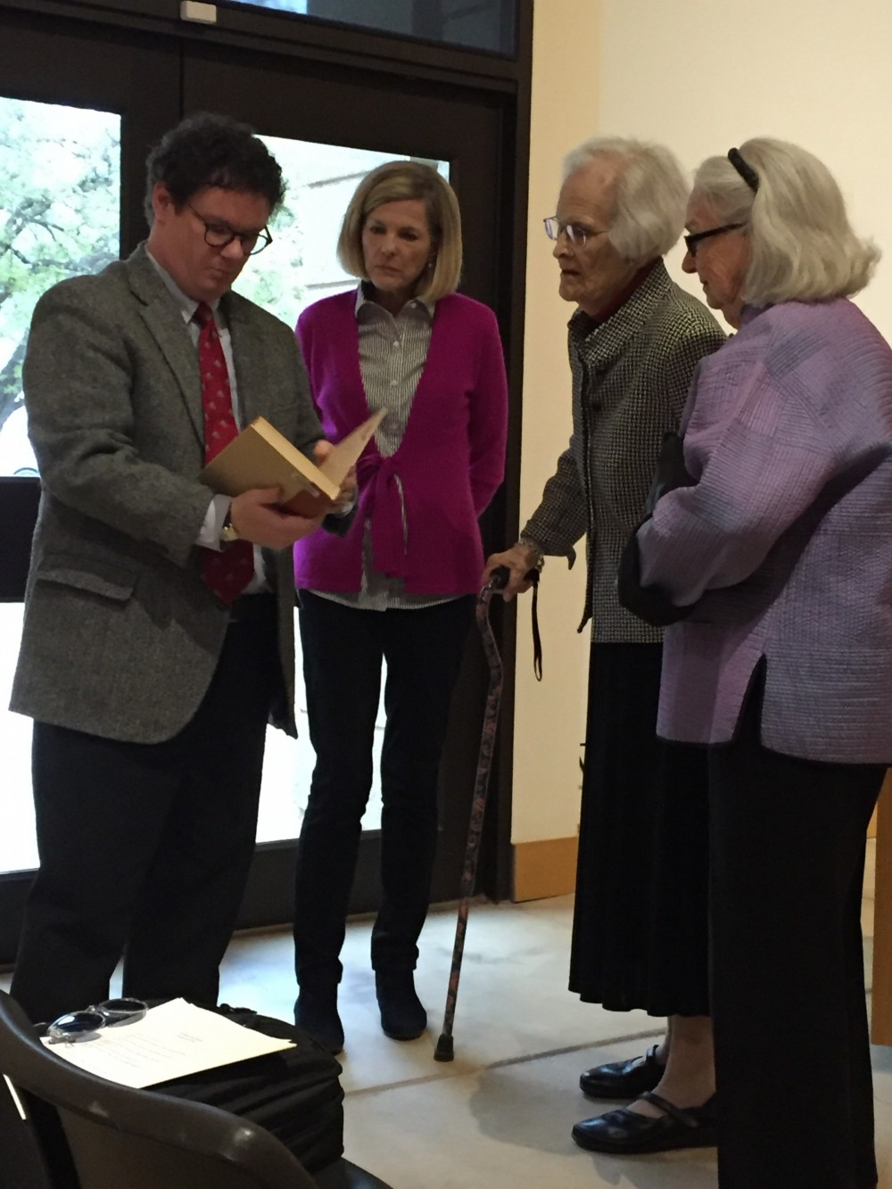 Jason discussing a copy of Interwoven with members of the Reynolds-Matthews family