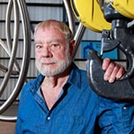 West Oakland-based sculptor Bruce Beasley poses for a photo with one of his Stainless steal ringe...