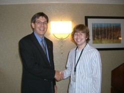 Sean Watson shakes hands with Dr. David Sutherland, president of PME