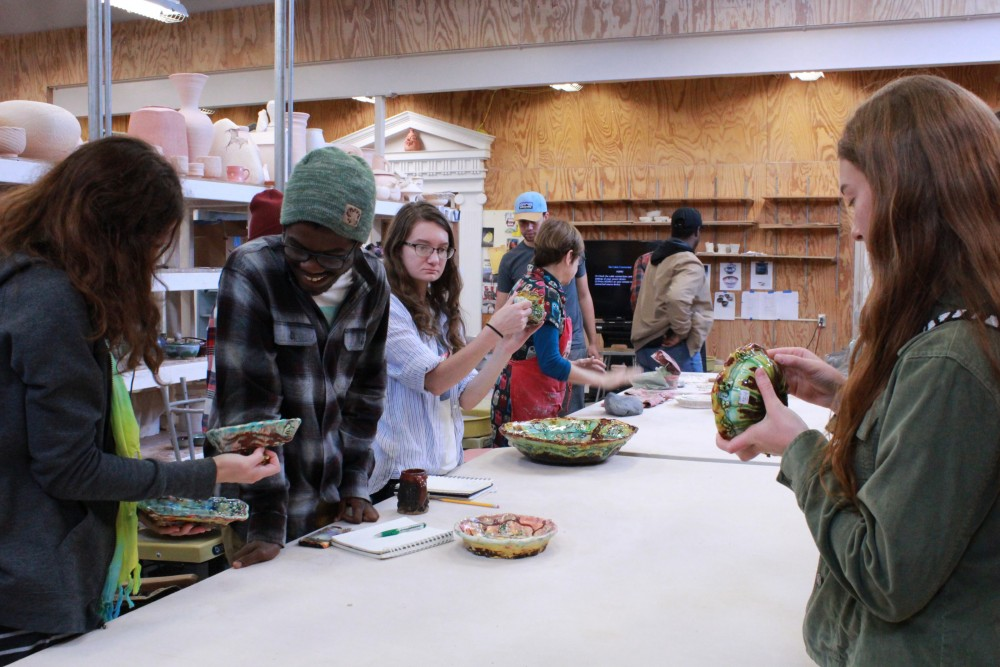 Students examine Lisa Orr's intricate pottery.