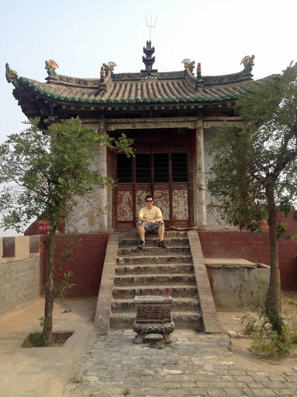 Clayton Tucker sits on the steps of a mountain temple near the city of Yuncheng in Shanxi Province.