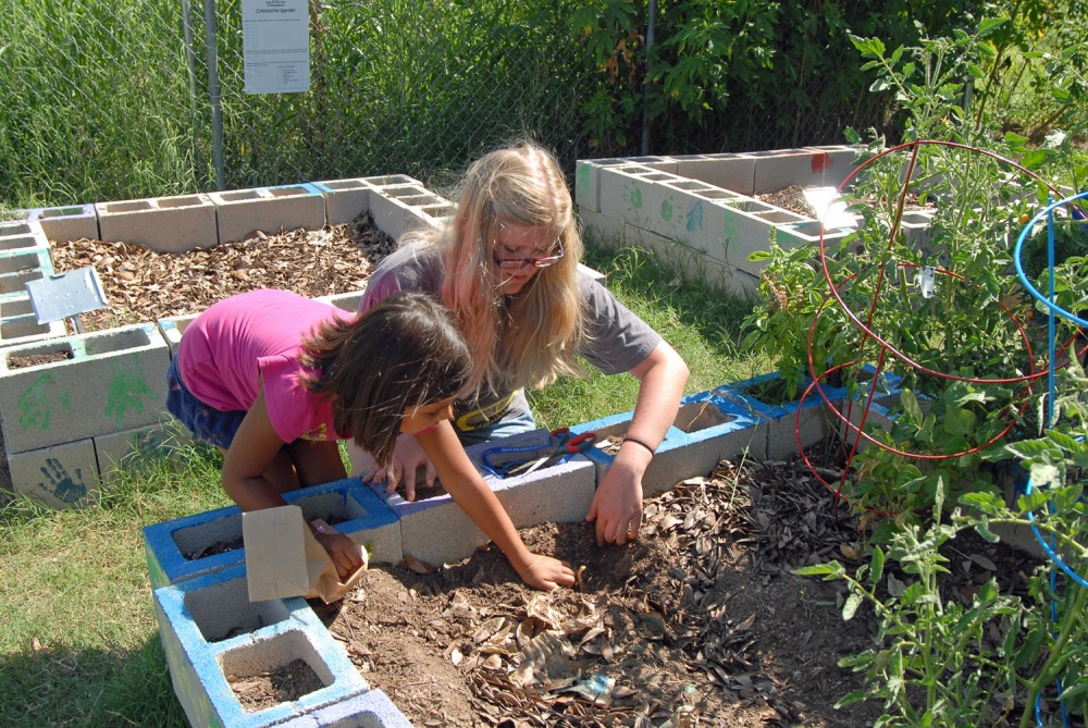 Elizabeth Funk works with a girl in the garden at the Boys & Girls Club during the summer of 2012.