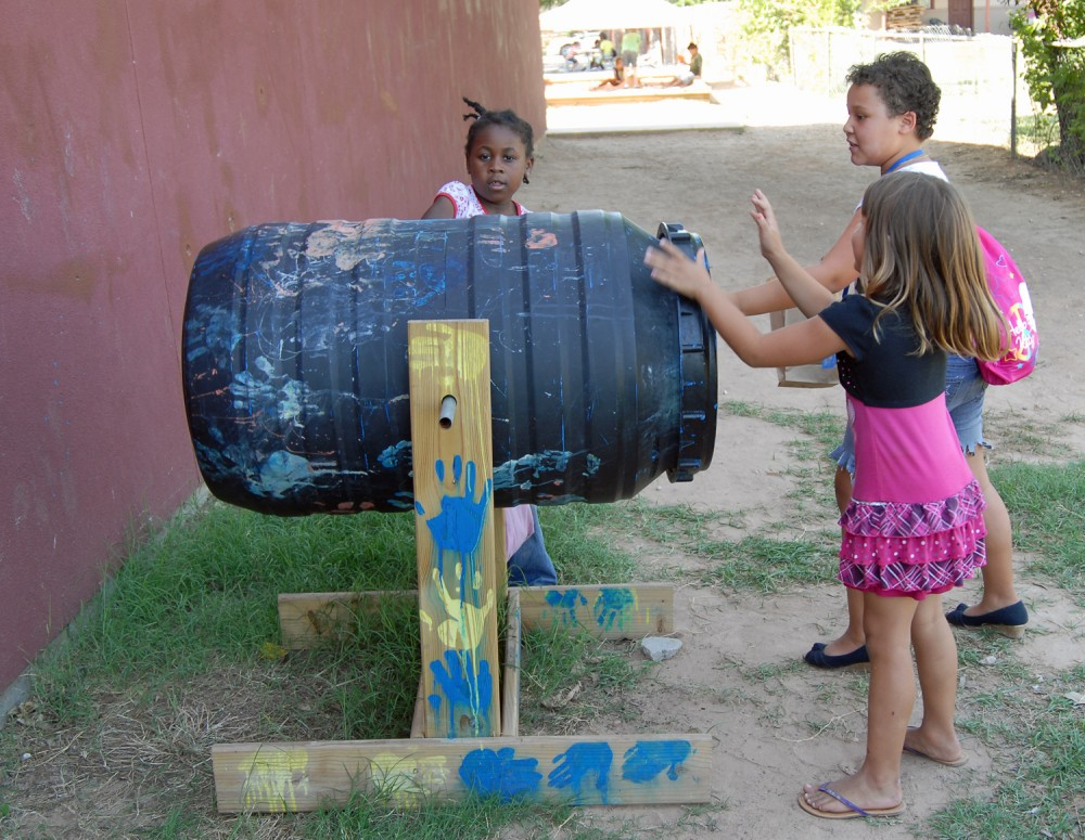 Students try their hand at rotating the composter.