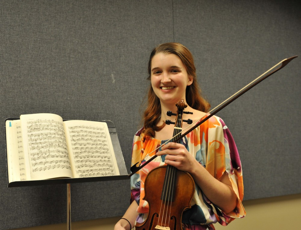 Marie Smith stands with the Baroque violin she has rented with the help of a grant from the King Creativity Fund.