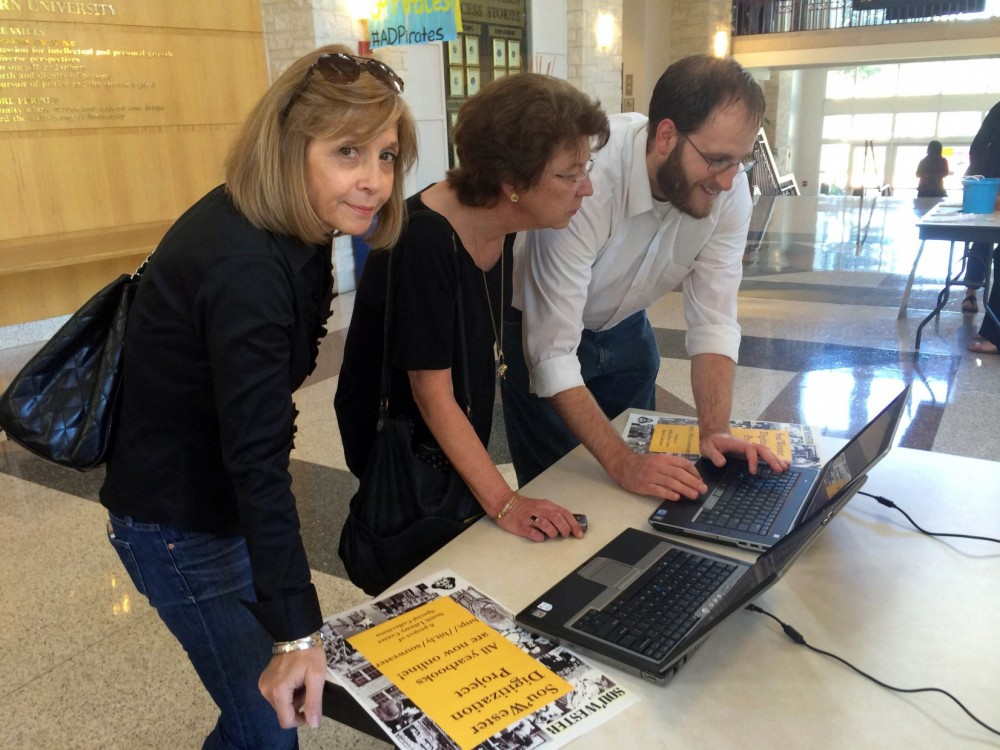 Jesse Saunders from Special Collections (right) shows alumnae Karen Hanson-Flowers and Karen Ray Fox how to find the old y...