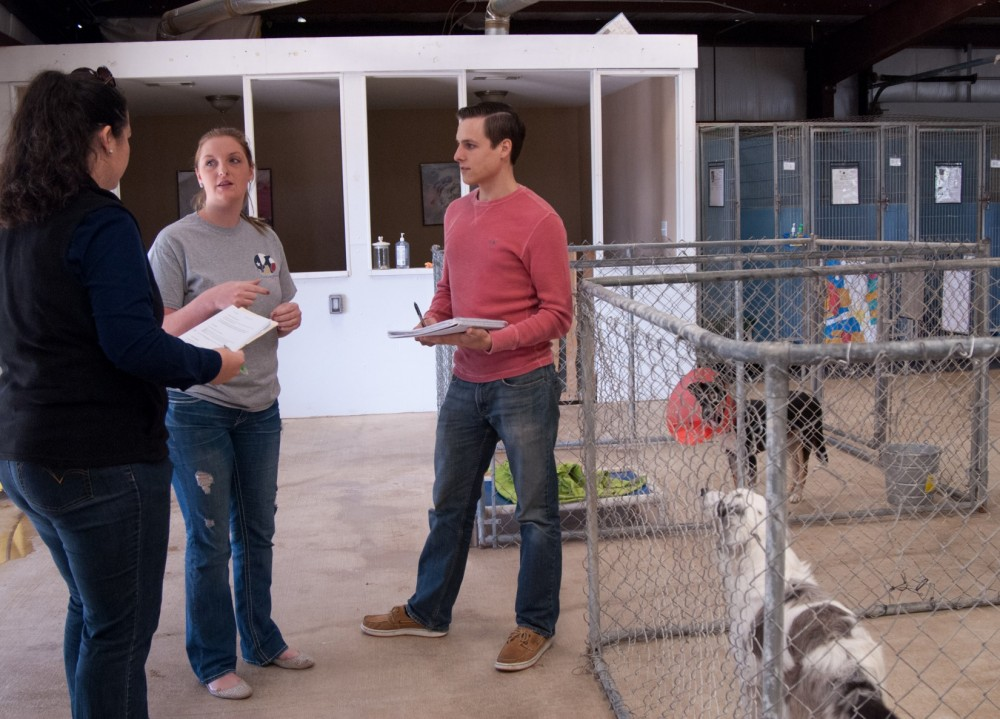 Business majors Hope Brown (left) and Nick Moore, talk with Danielle Cloud, the animal care manager for Texas Humane Heroe...
