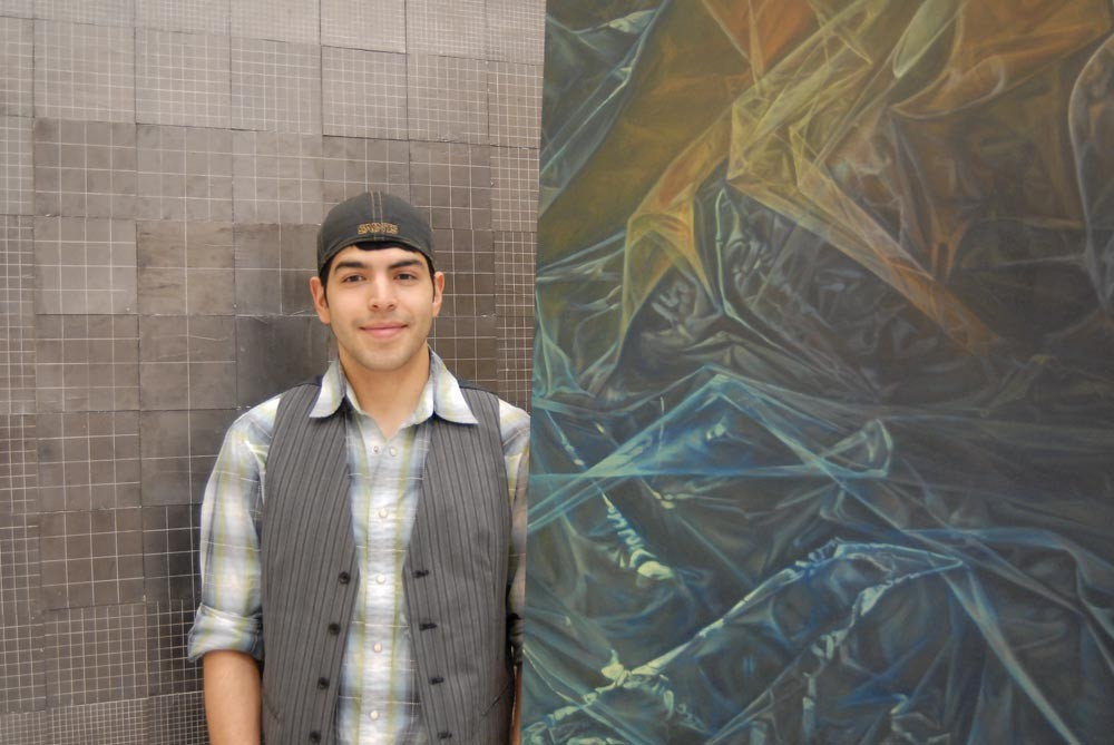 Ricardo Levario stands with his two paintings that were accepted for publication in Creative Quarterly.