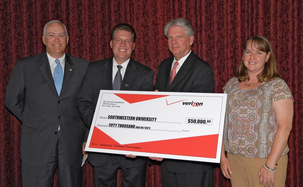 David Russell and Carl Erhart from Verizon present Southwestern University President Jake B. Schrum with a check to fund t...