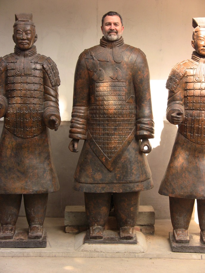 Music Professor Bruce Cain stands with models of the Xi'an warriors.