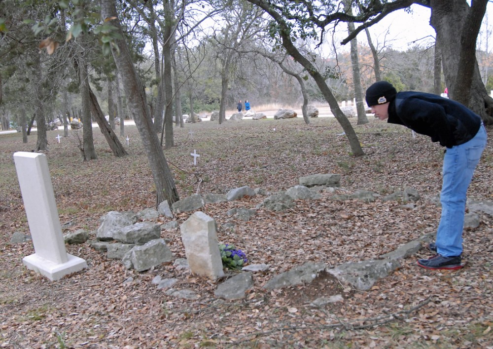 Andrew Snyder looks at a hand-marked grave in the black section of the Old Georgetown Cemetery. English Professors Carina ...