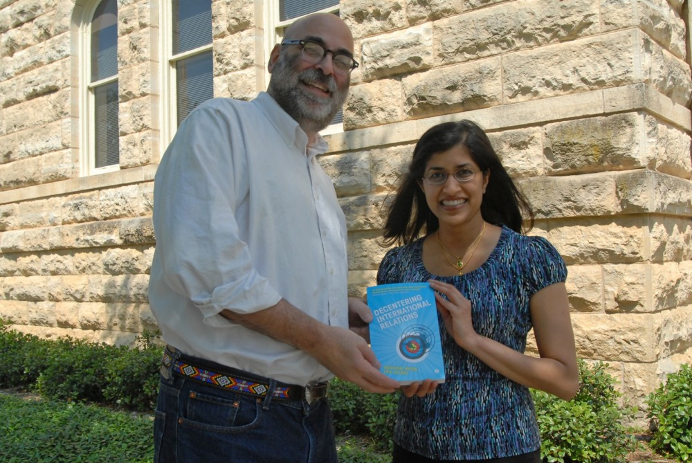 Political Science Professor Eric Selbin and 1997 graduate Meghana Nayak display the book on international relations that t...