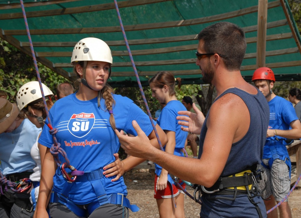 Instructor Elliot Pervinich helps Carly Cooper get ready for the climbing wall.