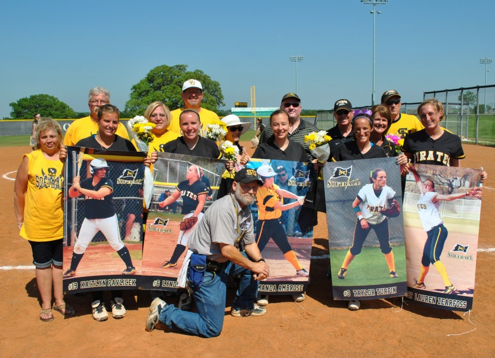 Graduating seniors on the softball team pose for a group photo after they were recognized April 1. (Photo by Karlis Dunens)