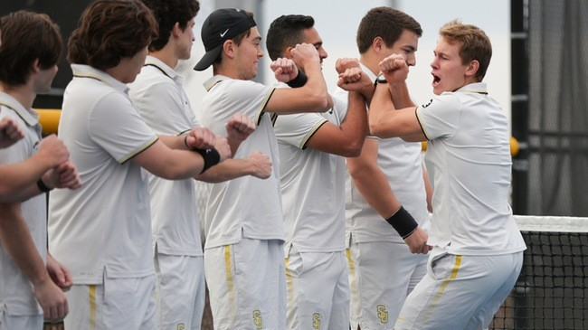 Dimanche, captain of the SU men's tennis team, rallies his fellow players at the beginning of a m...