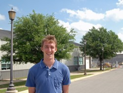 2010 graduate Nathan Shaw-Meadow stands in front of some of the lights his company retrofitted on campus as part of a proj...