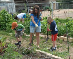 Staff member Paulette Butterworth works win her son, Drew (right), in the community garden.