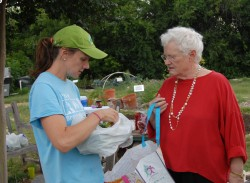 Molly Jensen (left) shows staff member Lou Ann Moore what is in her first bag of produce from the garden.