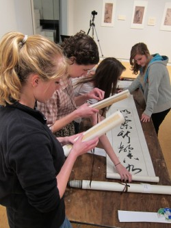 Students in Kristen Van Patten's Exhibition Practicum class unroll calligraphy scrolls for the exhibit they had to stage...