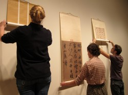 Julia Page, Tess Outlaw and Kristen Van Patten hang scrolls for the exhibit.