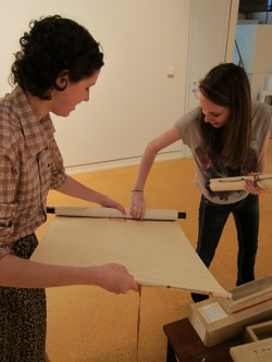 Tess Outlaw and Marion Clendenen unroll a scroll to be exhibited.