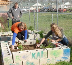 Sarah Puffer (right) helps plant the new garden at the Boys & Girls Club of Georgetown.
