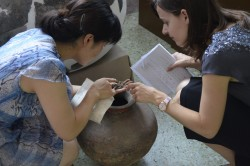 Art history professor Allison Miller looks at food and charcoal remains from a recently excavated Han dynasty pot found in...