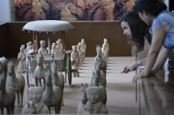 Art history professor Allison Miller and Li Fang, director of the Zhangqiu City Museum, examine terracotta figurines excav...