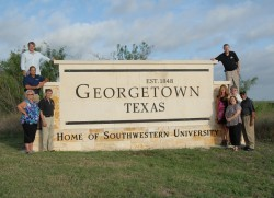 Members of the College Town Committee stand around the sign near campus that was recently changed to note that Georgetown ...