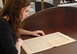 Junior communication studies and art history major Maryhelen Murray looks at an issue of the Megaphone from 1913 in Specia...