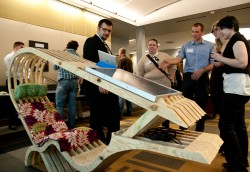 Amir Hessabi (left) and Chandler Johnson show off a prototype of their solar lounge chair at the 2014 Research and Creativ...