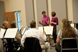 2013 graduate Stacie Glowka receives some pointers on conducting from Peter Bay, music director of the Austin Symphony, at...