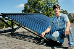 Phi Delta Theta alumnus Jeff Bedall stands next to the solar collector he installed on top of the fraternity house.