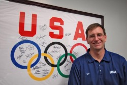 Scott McLean stands with a banner that members of the U.S. Olympic Swim Team signed for him.