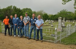 Members of the Physical Plant staff who helped with the project stand by the restored fence (Photo by Carlos Barron).
