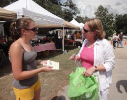 Kira McEntire visits with a resident at the Georgetown Farmers Market (Photo by Shannon Hicks).