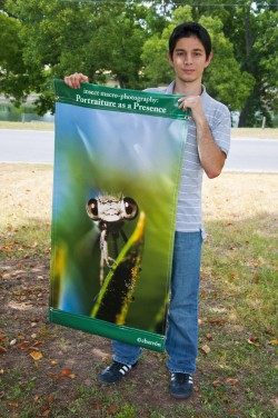 2010 graduate Carlos Barron displays one of the banners that are on display at Rivery Park.