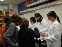 Megan Lowther, Catherine Martin and Rachel Sellari work with students at Mitchell Elementary School on a chemistry experim...