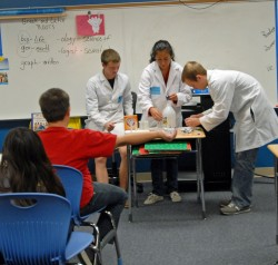Megan Lowther, Catherine Martin and Rachel Sellari conduct an experiment with students at Mitchell Elementary School.