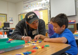 Sophomore biochemistry major Evan Perkins works with a bilingual student at Annie Purl Elementary School.