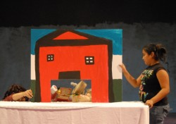 "Irene Lule (left) helps students stage a puppet show version of ""Little Red Riding Hood."""
