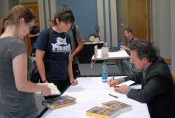 Lawrence Wright, author of the Pulitzer Prize-winning book, The Looming Tower, signs copies of his book after speaking at ...