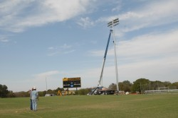 Workers make the final adjustments on one of the light poles that was installed on the varsity soccer/lacrosse field.