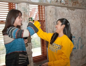 December graduates Marisol Frausto-Martinez and Celia Campos congratulate each other after signing the Cullen Tower, which is a tradition for seniors who make a pledge to the senior class gift. Frausto-Martinez and Campos both earned degrees in biology. December graduates will be recognized Dec. 14.