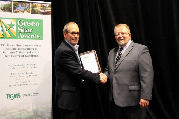 Manager of Facilities Services Randy Erben accepts Honor Award from The Professional Grounds Management Society.