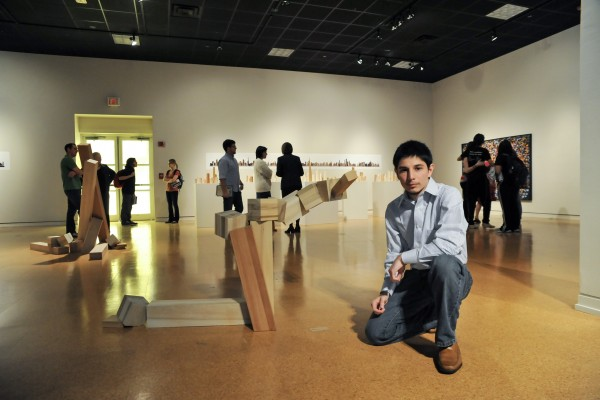 Carlos Barron '10 with his sculpture at his senior art exhibition.