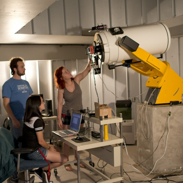 Physics professor Mark Bottorff (left) looks on as Francis MacInnis, Raina Musso and Taylor Hutchison prepare the Fountainwood Observatory research telescope for a night of observing black holes. (Photo by Lucas Adams)