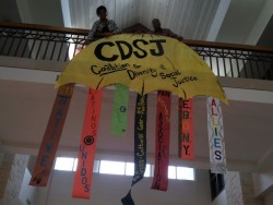 Two CDSJ members, Auburney Jackson and Colin Daniels, in the process of hanging a visual representation of CDSJ's structur...
