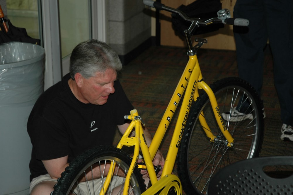 President Jake B. Schrum helps assemble bikes from a Pirate Bike shipment.